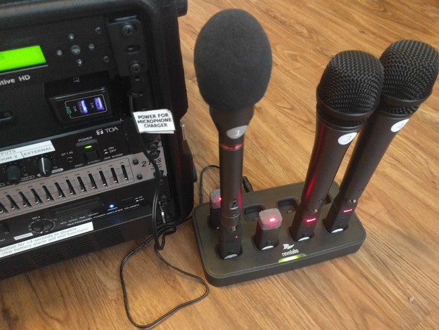 A close-up view of the Revolabs microphone charger with five microphones inserted and power indicators lit